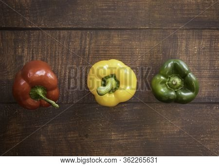 Red, Yellow And Green Bell Pepper On A Wood Plank Background
