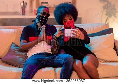 Young African man in black face bandana keeping hands together by chest while sitting next to girl with red nikab making selfie