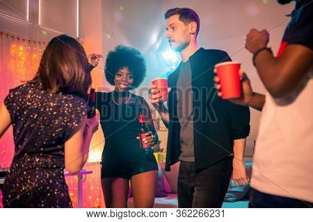 Young cheerful African woman with bottle of beer dancing among her friends with drinks while enjoying party at home