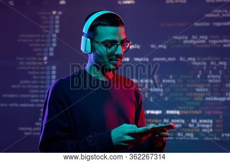 Serious advanced young Arabian tester in wireless headphones examining new app on gadget, coding background