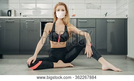 COVID-19 and life at home. Pretty young woman in medical mask does gymnastics while staying home during quarantine. Healthcare and sports.