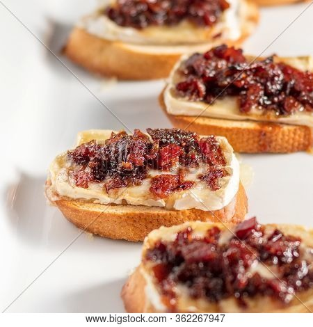 Cranberry Bacon Jam And Brie Crostini On A White Plate