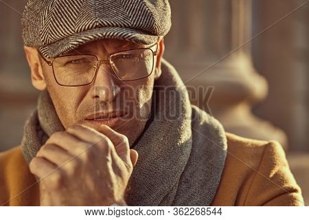 Portrait of a handsome middle aged man in elegant clothes and glasses standing on the street. Men's beauty, fashion. Optics style.