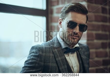 Handsome man in elegant checkered suit and sunglasses in a modern loft interior. Luxurious lifestyle. Man's fashion.