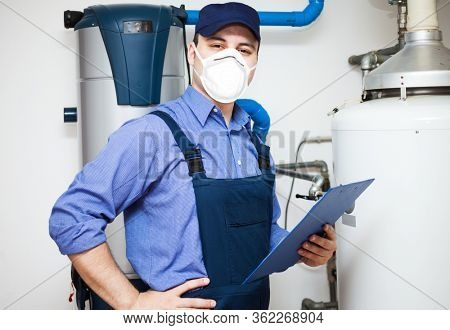 Smiling technician servicing an hot-water heater during coronavirus pandemic