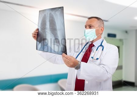 Doctor wearing a mask while holding a lung radiography, coronavirus and pneumonia concept