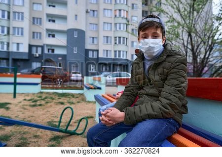 teen boy sits on a bench on playground near high-rise buildings with apartments, a medical mask on his face protects against viruses and dust