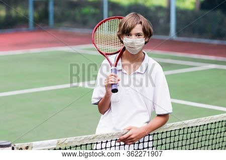 Boy In Face Mask Playing Tennis On Outdoor Court During Coronavirus Outbreak. Teenager With Tennis R