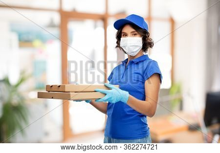 health protection, safety and pandemic concept - delivery woman in face protective medical mask and gloves with pizza boxes over office background