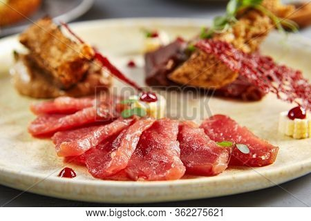 Meat appetizer in beige ceramic plate. Jerked beef and pork with baguette and onion sauce close up. Peas twigs decorations. European cuisine restaurant food, menu meal, served gourmet appetizer