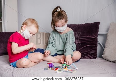 Two Children Collect Constructor In White Medical Masks Sitting On A Sofa .leisure And Entertainment