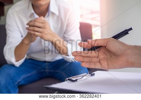 The Image Focuses On The Psychiatrist's Hand. The Clipboard Records The Illness. Is Healing The Mind