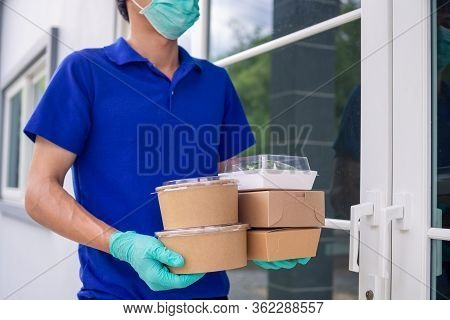 The Shipper Wears A Mask And Gloves, Delivering Food To The Home Of The Online Buyer. Stay At Home R