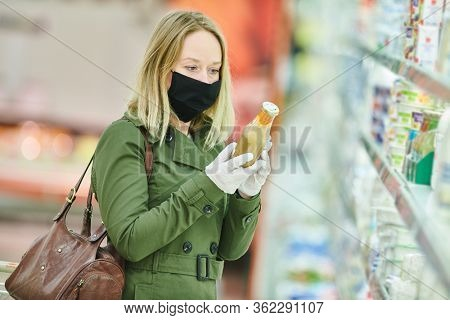 woman shopping dairy food supermarket in mask and protective gloves at coronavirus covid-19 outbreak