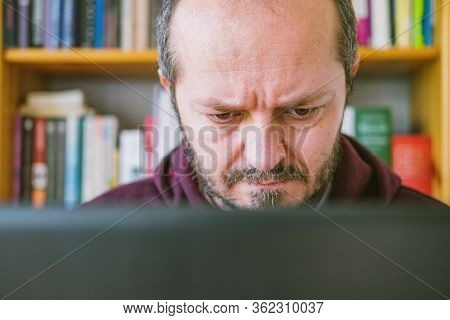 Adult Man Working From Home Office. Bearded Man Dedicated Working Online From Home On Computer Lapto