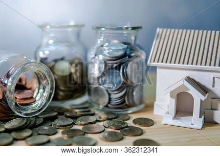 House Models With Coin In Currency Glass Jars And Spilling On Wooden Table. Saving Money For Future