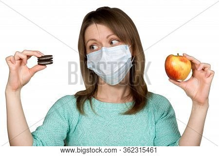 Young Woman In Face Mask Is Choosing Between Sweets And Apple. Concept Of Healthy Eating During Quar