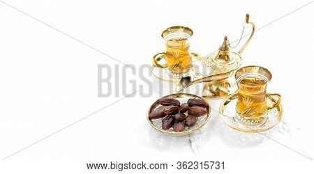 Tea Glasses With Dates And Golden Lantern Decoration. Oriental Hospitality. Ramadan Kareem