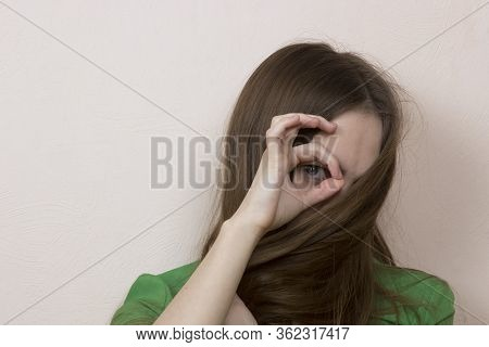 A Long-haired Girl Hides Her Face Behind Her Hair, Only One Of Her Eyes Is Visible.