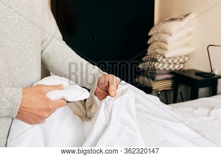 closeup of a young caucasian man inserting a duvet into a white duvet cover as he is making the bed