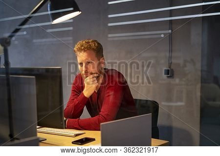 Tired and depressed businessman sitting at desk. Tensed business man with hand on chin working at computer late in modern office. Stressed man thinking about solution at computer, overworked.