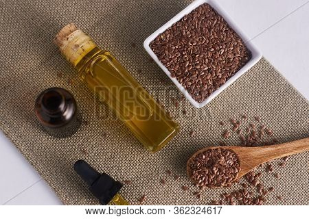 Linseed Oil With White Background And Linseed In A White Cup