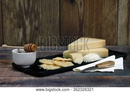 A Black Appetizer Tray With Parmesan Crisps, Wedges Of Parmesan, Grated Cheese And A Bowl Of Honey.