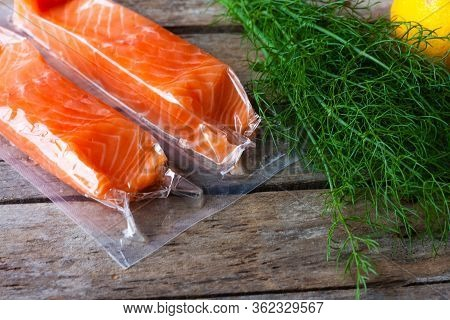 Red Fish O Salmon Fillets In Vacuum Package On Wooden Background. Fresh Fish, Lemon And Dill For Coo