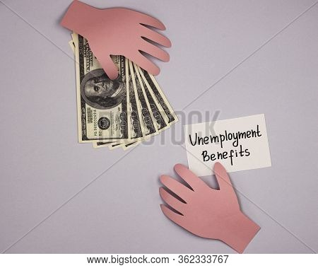 Hands Of Paper Holding Money And The Inscription Unemployment Benefit. The Concept Of Issuing Insura