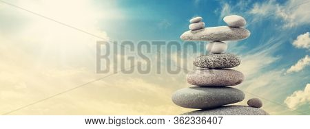 Pyramid of sea pebbles over a sunny sky. Life balance and harmony concept