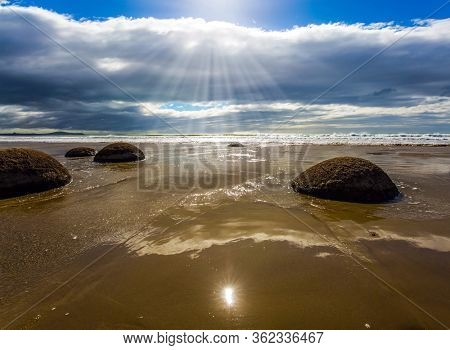 Moeraki Boulders is the group of large spherical boulders. Low tide in the Pacific ocean. The South Island of New Zealand. Popular tourist attraction. The concept of exotic and ecological tourism