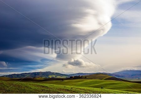 Gorgeous clouds over Tuscany hills. Agritourism. Rural farms and  picturesque hills of Tuscany after harvest. The concept of active, rural and photo tourism