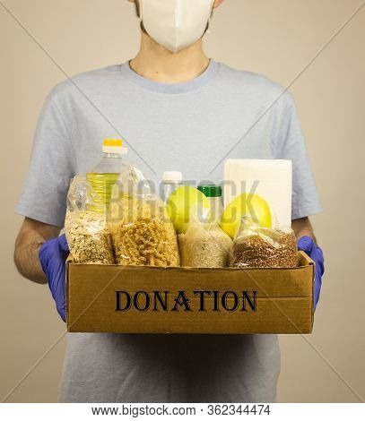 Donation. Donation Box. The Guy In Gloves And A Mask Holds A Box With Donation Products. Food Donati