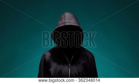 Portrait of computer hacker in hoodie. Obscured dark face. Data thief, internet fraud, darknet and cyber security .