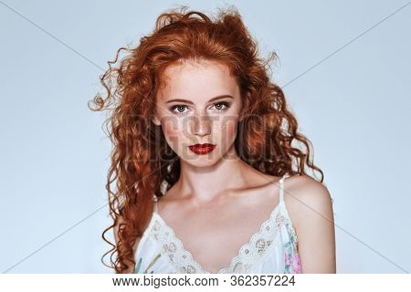 Beautiful young woman with long red hair. Hair care, hair coloring. Copy space.