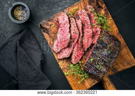 Traditional Commonwealth Sunday roast with sliced cold cuts roast beef with thyme and spice as top view on a rustic wooden cutting board