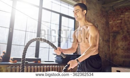 Young athlete in training with ropes against background of large window in gym. Lensflare effect