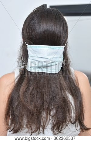 Medical Mask And A Joke With Hair Beautiful Girl. Joke Female Beauty And Mask. Girl Puts On Hair A M