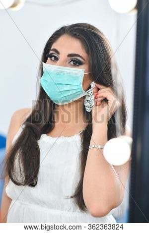 Medical Mask And A Beautiful Girl. Female Beauty And Mask. Girl Puts On A Mask Near The Mirror. Medi