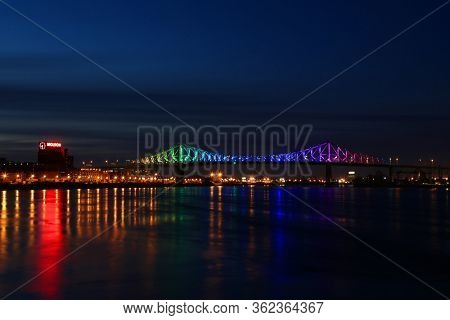 MONTREAL-CANADA, APRIL 20, 2020:  Beautiful view of Jacques Cartier bridge with rainbow colours during the corona virus in Montreal in Canada with reflexions in st-Lawrence river