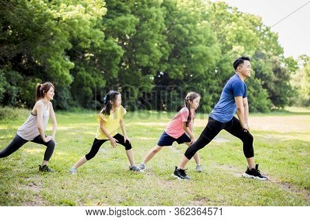 Happy Family Exercising  Together At The Park