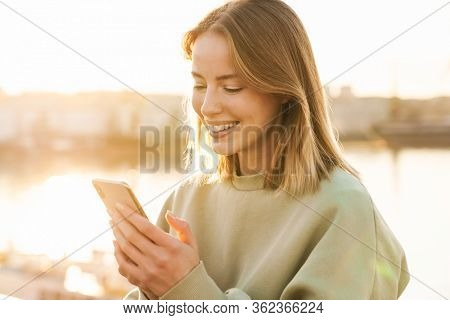 Portrait of cheerful caucasian woman smiling and using cellphone while walking on promenade