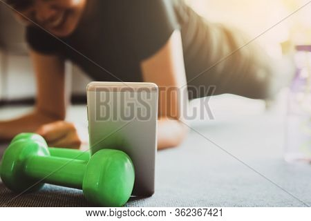 A Sporty Woman Using Smartphone During Workout At Home In The Living Room. Online Personal Trainer O