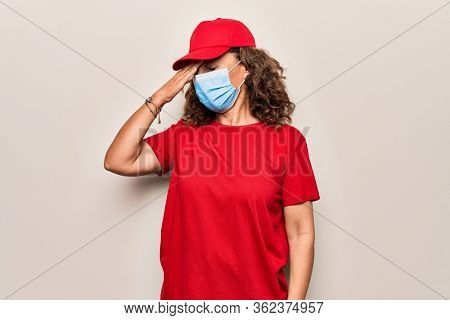 Middle age delivery woman wearing red cap and coronavirus protection mask surprised with hand on head for mistake, remember error. Forgot, bad memory concept.