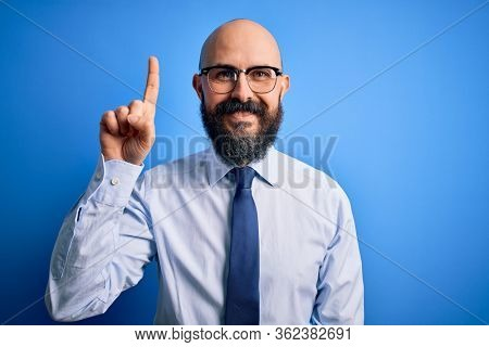 Handsome business bald man with beard wearing elegant tie and glasses over blue background showing and pointing up with finger number one while smiling confident and happy.