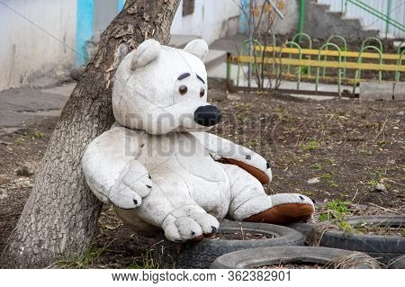A Sad Plush Toy Of A White Dirty Big Teddy Bear, Lost And Forgotten. Bear Alone On The Ground. Love