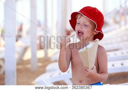 Little Boy In Red Panama On The Beach Eats French Fries