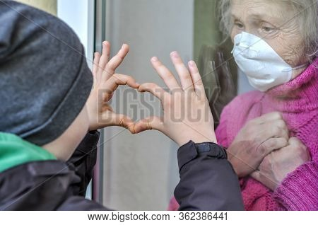 Grandmother Mature Woman In A Respiratory Mask Communicates With Her Grandchild Through A Window. El