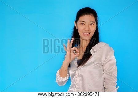 An Attractive Young Asian Woman Making An Okay Sign With Her Right Hand To Confirm That Everything I