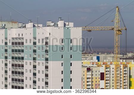 Construction Crane And Built Multi-storey Residential Building Against The Background Of Built-up Ci